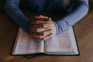 hands clasped over bible. Freedom of religion includes freedom from religion.